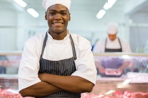 black man in butchery uniform smiling